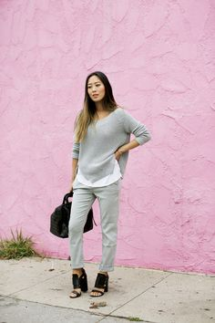 Aimee Song is wearing a grey zip detail sweater from French Connection and grey slouchy jeans from AG