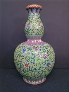 """A Qing dynasty green double gourd porcelain vase covered with scattered folly flowers spread by elaborate tied of floral springs, interior and the base covered in a blue glaze saved for the Qianlong reign period 4-character double frame seal mark in a white square. 15""""H x 8""""D"""