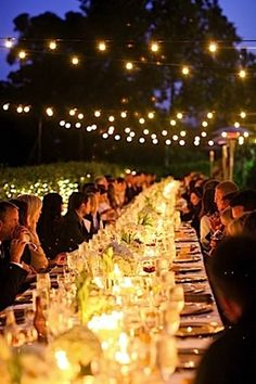 Candle glow at the center of the tables creates intimacy at long tables.