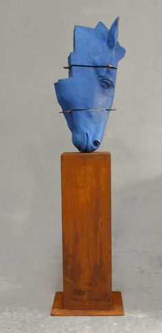 Blue horse on pedestal, I love the color of the head and the wooden pillar together.