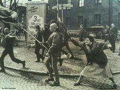 Woman hitting a skinhead with her handbag. She was reportedly a survivor of a concentration camp in WW2. Sweden, 1985