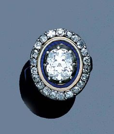 An early 19th century diamond and enamel ring, circa 1820. The central cushion-shaped diamond with blue and white enamel border detail to the cushion-shaped diamond surround