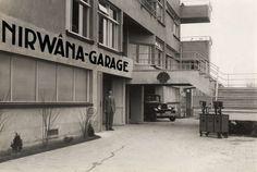 Autohandel. Nirwâna Garage gevestigd onder een flatgebouw aan de Benoordenhoutseweg in Den Haag. Op de trapopgang het logo van Shell met de tekst : Shell auto olie depot.De olie wordt geleverd vanuit de verrijdbare pompen rechts. Foto 1930.