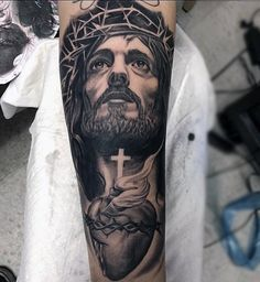 Man With Tattoo Of Jesus Holding Cross And Heart Forearm Sleeve