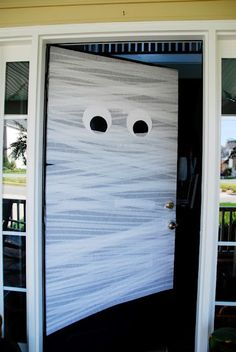 Mummy door made with white streamers and giant construction paper eyes.  So easy.