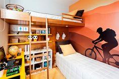 """Apesar de poucos elementos decorativos, este quarto projetado para dois irmãos de 6 e 11 anos ganha personalidade com a bicicleta que parece andar sobre a cama. """"O adesivo que cobre toda a parede tem como objetivo dar um tom aventureiro e estimular os esportes"""", explicam os arquitetos Marcello Sesso e Débora Dalanezi."""