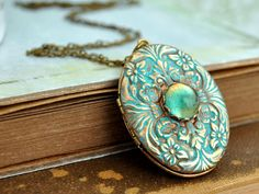 Beautiful vintage 70s brass locket decorated with vintage 50s blue glass cab sets in center. Lace setting torch soldered on the locket, applied faux