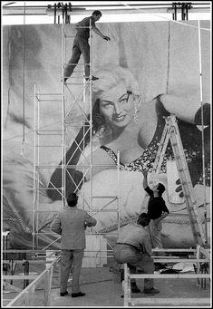 Federico Fellini supervises a poster of Anita Ekberg being hung (for the film Boccaccio '70), photo by Elio Sorci, Rome, 1961