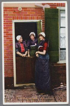 Bunschoten Spakenburg Een buurpraatje. Drie vrouwen in rouwdracht bij de deur. Twee staande vrouwen achter de onderdeur met de gehaakte muts strak over het hoofd, korte kraplap, donkere boormouwtjes, een vrouw zonder rode doek. Voor de deur een jonge vrouw met paarse kraplap en kulder in onjuiste kleur. Een blauw schort met blauwgeruit stukje. 1930-1933 #Utrecht #Spakenburg