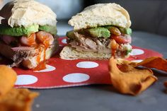 yummy pulled pork and avocado sandwich with some spicy hot sauce and a few chips inside. @Heather Christo