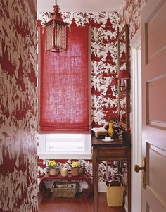 Delightfully busy and engaging Jardin Chinois Red wallpaper from Waterhouse Wall-hangings masks the flaws of an awkwardly shaped powder room. The window shade is Cire red linen by Lee Jofa with Clarence House Greek Key tape. The perfect example of a bold use of red and white.