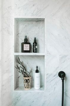A marble shower niche fitted with tow shelves is framed by staggered honed marble wall tiles. Tile Shower Niche, White Subway Tile Shower, Subway Tile Showers, Bathroom Niche, Marble Showers, Master Bathroom, Subway Tiles, Washroom, Built In Shower Shelf