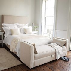 neutral bedroom with a daybed at the foot of the bed.