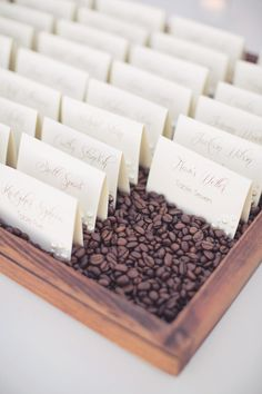 Perfect for coffee lovers! Name tents in a tray filled with coffee beans. // wedding escort cards