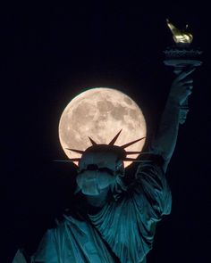 The Statue of Liberty kept company by the moon.