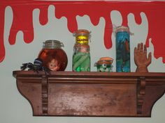 "Two dollar-store red plastic tablecloths became a border of oozing blood all around the dining room. At the buffet table, another tablecloth was trimmed the same way and used as a topper over white...food was served on a table ""dripping"" with ""blood""! The shelf displayed jars of creepy things floating in colored water."