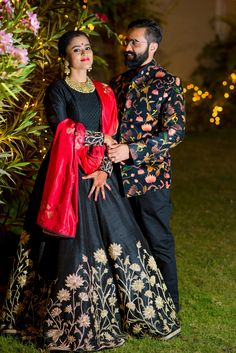 Sangeet Lehengas - Black Lehenga with Red Dupatta | WedMeGood | Bride in a Black SIlk Lehenga with Gold Zardozi Embroidery and a Red Dupatta and the Groom in a Black Floral Bandh Gala with Black Pants #wedmegood #lehenga #indianbride #indiangroom #indianwedding #black