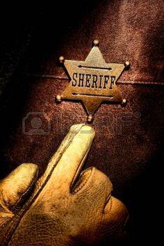 West americano leggenda uomo di legge che punta con il dito e la mano che indossa un vecchio guanto occidentale per il suo sceriffo distintivo sul petto per far valere la sua legge dovere legale photo