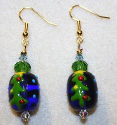 Handcrafted by Teal Palmetto, LLC. These holiday earrings have an unusual but lovely mix of colors.  The glass Christmas tree focal beads are blue and are handpainted in red, blue, yellow, and green. Each earring sports a green glass accent bead, as well as two Swarovski crystal beads, one clear, and the other in light teal to give this pair extra sparkle.  They have gold fish hook ear wires. Price: $16.