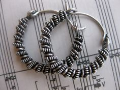 Small wire wrapped sterling silver earrings hoops by kattaca          Love the use of sheet music for background