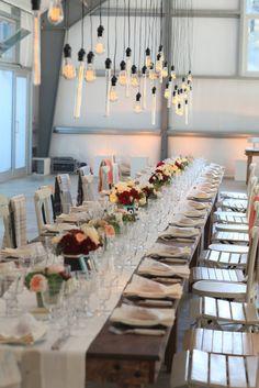 Long table setting with hanging Edison bulbs