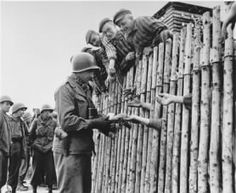 Army Corporal Larry Matinsk of the Infantry Division hands out cigarettes to inmates at Allach concentration camp on the day of their liberation (April Allach was a sub-camp of the Dachau concentration camp complex. Holocaust Memorial, Holocaust Survivors, Holocaust Unit, Gi Joe, Buchenwald Concentration Camp, Lest We Forget, World History, World War Two, Wwii