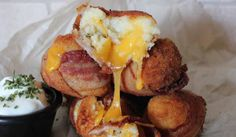 Křupavé bramborové kuličky se slaninou a sýrem Ingredience  2 hrnky bramborové kaše (studené) 1 vejce slanina (na jednu bombu – 1 plátek slaniny) 1/2 šálku strouhanky sýr čedar nakrájený na kostičky sůl, pepř, bylinky podle chuti (např. bazalka, pažitka, česnek, tymián) olej na smažení špejle či párátka zakysaná smetana na dresing