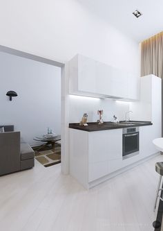 Modern White Kitchen Units With Brown Countertops And Sink Side By Side With The Entertainment Room.