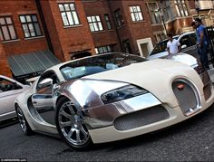 A Bugatti Veyron Centenaire - one of the most expensive cars to be made in the world drives past admiring onlookers
