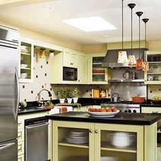 Celadon green cabinets, black countertops, stainless steel appliances, modern pendant lighting, tile backsplash.