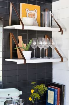 In one trailer, a black tile wall serves as the backdrop for the small kitchen. The darkness of the dramatic installation adds dimension and helps to ground all of the neon accents.