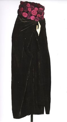 Madeleine Vionnet evening cape, summer 1918, model 32. Black silk crushed velvet, collar with appliqued crown of roses made of crushed mauve and fuchsia ribbon, gold lamé ribbon, slits for hands.