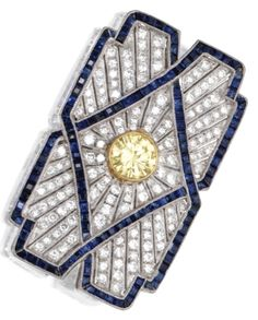 An Art Deco Platinum, Diamond, Coloured Diamond and Sapphire Brooch, Circa 1920. Set in the centre with a round diamond of light to fancy light yellow colour weighing approximately 1.00 carat, framed by old European-cut round near colourless diamonds weighing approximately 1.30 carats, accented by calibré-cut sapphires. #ArtDeco #brooch
