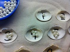 Summer activity.   Have the kids put pearls according to the matching number in the seashell. Sensory bin idea too.