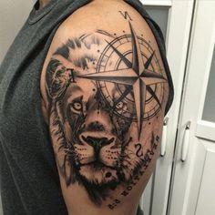 ein großer schwarzer löwe und ein großer schwarzer kompass auf dem schulter idee für einen compass tattoo für männer