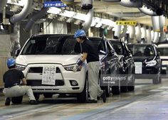Workers make a final inspection of a Mitsubishi Motors Corp. RVR sports utility vehicle (SUV) on the production line of the company's plant in Okazaki City, Aichi Prefecture, Japan, on Wednesday, Aug. 10, 2011. Japanese exporters called for more action to weaken a near-record high yen even after government intervention prompted the currency's biggest drop since March. Photographer: Tomohiro Ohsumi/Bloomberg via Getty Images