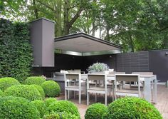 Deze buitenloft is door inzet van minimale ontwerpmiddelen een fraai architectonisch element in de tuin geworden. Een zwevend dakelement vormt een overdekt terras, samen met de achterwand bekleed m…