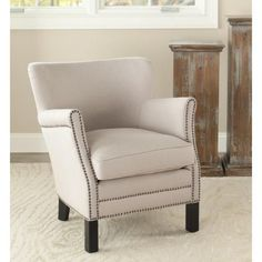 Add an extra seating option to your living room with this comfy club chair. It comes with a strong wooden from with a rich mahogany finish. The beige color and attractive nailhead accents can easily be coordinated with a room's interior design.