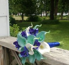 This listing includes 1 Bouquet with 24 White & Aqua Blue real touch calla lilies, with Real Touch Sonia Royal Blue Orchids wrapped in Royal Blue satin ribbon with Blue Diamond Pins in the Calla Lilie