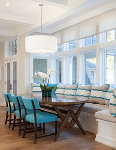 white dining room with turquoise chairs