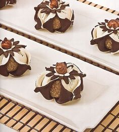La pâte : 1/4 de mesure de margarine fondue Eau de fleurs Vanille Cacao 3 mesures de farine (300 gr) La farce : 300 gr d'amandes non-émondées 100 gr de sucre cristallisé 1 noix de beurre Vanille 1 oeuf battu Décoration: Miel Noisettes 1- Préparer la pâte...