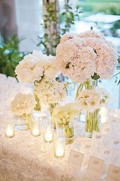 The table is set with a beautiful array of white floral arrangements in clear vases of varying sizes. Flowers range from hydrangeas to peonies to calla lillies.