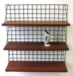 Teak wandrek/boekenrek, zwart rasterwerk achterwand met zwarte metalen dragers waarop drie teak houten plankjes rusten. Het wandrek is in een zeer goede staat. Zeer unieke variant op het tomado