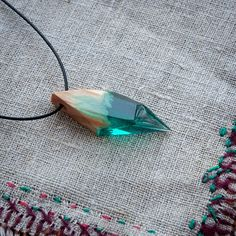 Modern aquamarine color wood resin minimalist necklace made in geometric style of the jewelry. This glowing cosmic pendant is colored into outstanding blue green, which is very light-dependent. Its appears from Emerald blue(outside the bulidings) to Sea blue color with a green