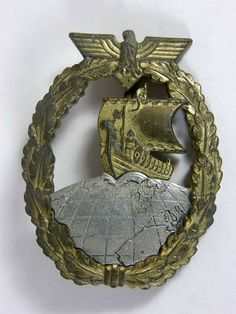 Kriegsmarine Auxiliary Cruiser badge by Schwerin Berlin. Second pattern with aluminum globe and zink eagle and wreath. Schwerin Berlin marked on reverse displays single attachment rivet.