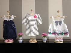 Use stands to display baby clothes for cute decorations
