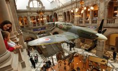 A mother and child look at the LA198 Spitfire on display in the Life Court of Kelvingrove Art Gallery and Museum