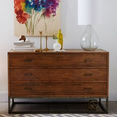 Made of solid pine with an iron frame base, the Copenhagen 3-Drawer Wide Dresser's grained wood surface is hand-planed to create a distressed appearance, and finished with a protective glaze. Three wide drawers and an open shelf provide plenty of storage space.