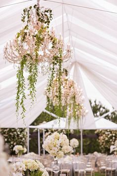 Under tent decorations, flowers/vines wrapped around chandeliers