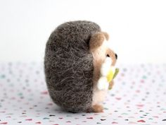 This adorable needle felted hedgehog holding a daisy is handmade with love out of 100% natural wool. This wooly woodland friend would make a perfect gift for a hedgehog lover, or can be used as a decorative item to add some woodland inspiration to your room, desk or living space. Measures approximately 5.5cm w x 6.5cm h (2.2w x 2.4h). ~~~~~~~ Item may vary slightly from the photos shown as each is handmade and one-of-a-kind. Item will be carefully packaged in a kraft gift box using recycl...